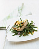 Fried zander with olives and parsley on green beans