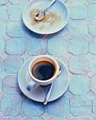 Cup of espresso and brown sugar on turquoise tiles