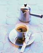 Espresso in silver cup and saucer with a small pot