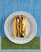 Roasted vegetables and herbs on slice of polenta