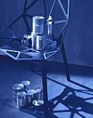 Verschiedene Konservendosen auf und unter einem Eisenstuhl