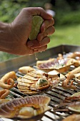 Sprinkling seafood on a barbecue with lemon juice