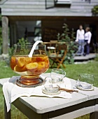 Peach punch and glasses on a garden table