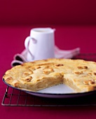 Apple and potato pie with a small jug of custard