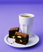 Pistachio brownies with a beaker of coffee