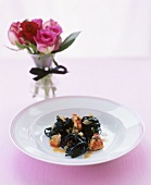Black linguine with lobster, small vase of roses