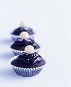 Three iced chocolate cupcakes with silver dragées