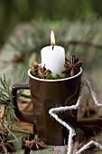 Kerze in einer Tasse mit Moos und Sternanis