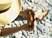 Woman sitting on pebbles with a sandwich