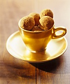 Chocolate chestnut truffles in gold cup and saucer