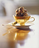 Amaranth and dried fruit truffles in a cup and saucer