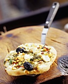 Mini-pizza topped with leeks, feta, herbs, anchovies, olives