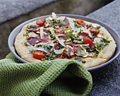 Pizza topped with dried goat meat, mushrooms and tomatoes
