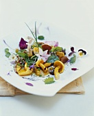 Wild herb salad with edible flowers and mushrooms