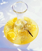 Elderflower punch with oranges and vanilla in a carafe