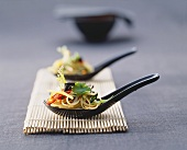 Asian noodle and vegetable salad on spoons