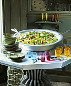 Large dish of mixed salad leaves, crockery and glasses