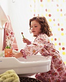 Little girl in bathrobe at wash basin with toothbrush