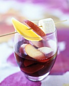 A glass of sangria with fruit skewer
