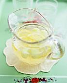 A glass jug of lemon punch with melon balls