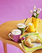 Croissant with two cups of cappuccino and tulips in a jug