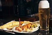 Cheese sausage with a glass of beer at a snack stall
