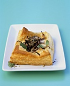 Goat's cheese and onion puff pastry tart with oregano