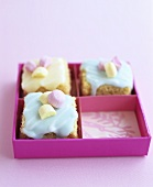 Small cakes with coloured icing in a gift box