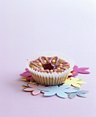 Muffin with iced flower on paper flowers