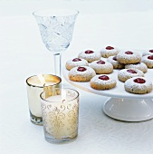 Jam biscuits on a cake stand with candle glasses