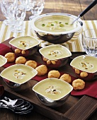 Cream of vegetable soup in tureen and bowls, pastries
