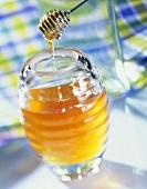 A jar of honey with a honey dipper