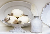 White still life with crockery, goose eggs and feathers