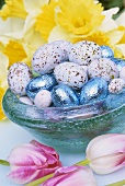 Easter eggs in blue glass bowl, spring flowers