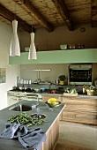 Moderne Küche mit Küchenblock, Steinboden und Holzdecke
