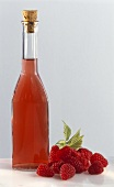 Bottle of raspberry vinegar with fresh raspberries