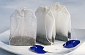 Three tea bags on a plate