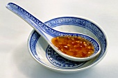 Sweet chilli sauce in porcelain spoon in small dish
