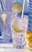 Two glasses of mineral water with ice and slices of lemon and lime
