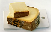Two pieces of Comté cheese on a wooden board