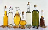 Seven different oils in bottles with the relevant raw materials