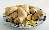 Fresh ginger on a plate, whole and pieces
