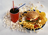 Unhealthy food: burger, chips, popcorn, cola, crisps