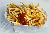 Dish of chips with ketchup, paper napkin and plastic fork