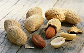 Shelled and unshelled peanuts on wooden background