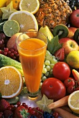 Glass of carrot and papaya juice surrounded by fruit and vegetables