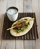 Mince kebab on lemon grass skewer with pea salad on bread