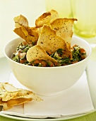 Tomato and cucumber salad with parsley and bread crisps