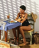 Young woman in swimsuit sitting at table with mixed salad