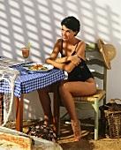 Junge Frau mit Badeanzug sitzt am Tisch mit buntem Salat